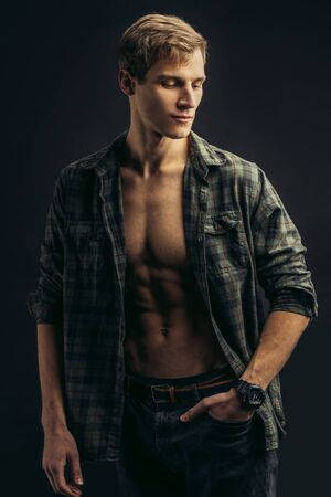 portrait of young caucasian fit man model with naked torso, checkered casual shirt on his muscular body, male looking side. perfect body of man