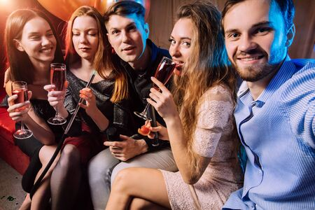 group of young people together in karaoke bar, singing and having fun together, clubbers rocking and chilling out in karaoke. celebration, holiday, birthday concept