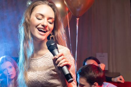 young emotional female singing in microphone in karaoke bar, wearing dress, friends with balloons celebrating in the background