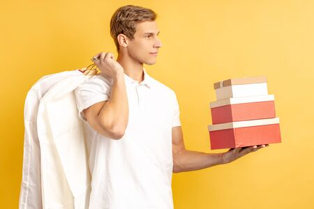 handsome attractive caucasian young delivery man in white unifrom holding red boxes and packed clothes on hanger, express delivery concept. yellow background