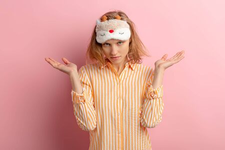 portrait of young and beautiful caucasian woman before sleeping, want to sleep, stand shrugging isolated over pink background, wearing pajamas and blinfold for sleep