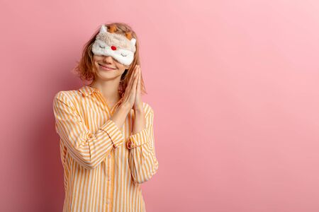 portrait of funny woman with short hair, wearing pajamas and blindfold on eyes, want to sleep, she doesnt get enough sleep at morning, isolated pink background