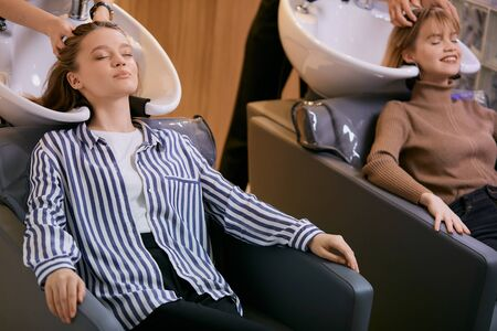 young caucasian girls enjoy and relax with closed eyes while professional stylists hairdressers wash their heads after successful dyeing in beauty saloon 版權商用圖片