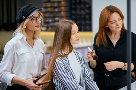 Beauty concept. professional hairdresser or hairdo doing her daily work in beauty saloon, doing stylish hair cut to young female