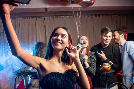 young woman take photo with friends in the background in karaoke bar, isolated over smoky space, smoking hookah Banco de Imagens
