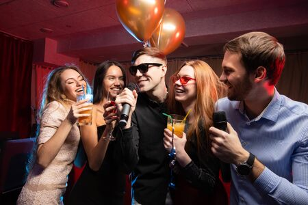 group of beautiful young caucasian people, guys and ladies chilling out in karaoke bar, have fun, spend free time together in karaoke, singing and communicating