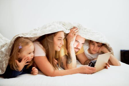 friendly caucasian family lying under blanket at home at morning, watching video on tablet, mother father and kids on bed in casual wear Reklamní fotografie