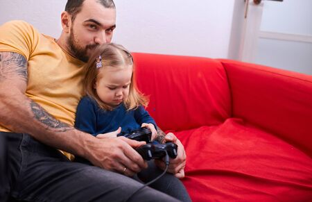 cute little child girl sit with playful joyful father while he is playing video games, sit on sofa. leisure, game concept