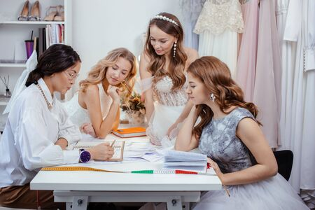 caucasian group of women gathered together in designers office to discuss new style of dress, young girls in trendy white wedding dresses