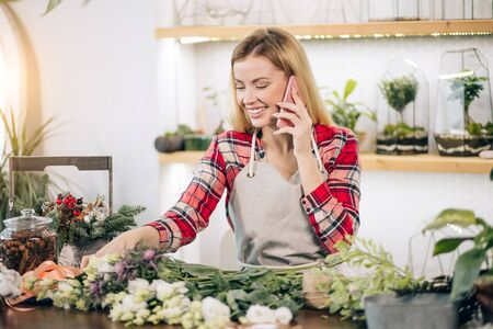 smiling cheerful caucasian lady with blonde hair, young florist talking on phone at work, while having free time, no customers at work. wonderful flowers lying on table Zdjęcie Seryjne