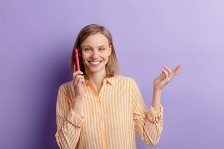 portrait of smiling, laughing young woman taking on phone with friend isolated over purple background. beautiful woman look at camera Zdjęcie Seryjne