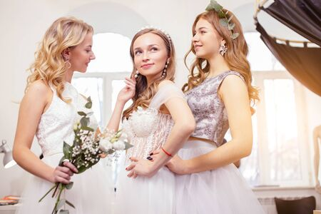 portrait of charming ladies future brides, wearing wedding dresses posing at camera together, beautiful young women of caucasian appearance in wedding salon Zdjęcie Seryjne