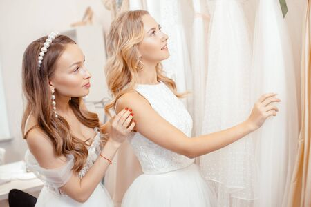 young caucasian friends choosing, trying on wedding dresses in salon, beautiful women preparing for wedding, to celebrate, dream to be bride Zdjęcie Seryjne