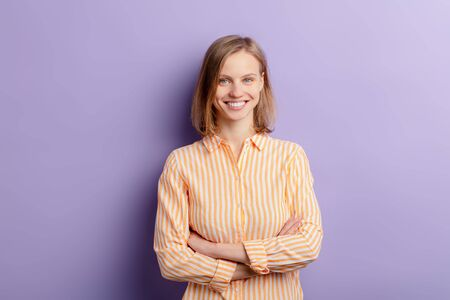 atractive caucasian happy young woman stand looking at camera, wearing casual clothing isolated over purple background