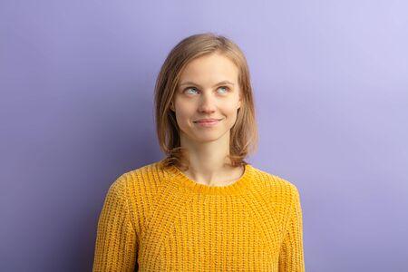 portrait d'une jeune femme rêveuse séduisante en blouse jaune décontractée pensant ou rêvant, levant les yeux, ayant les cheveux courts et une apparence caucasienne, isolée sur fond violet