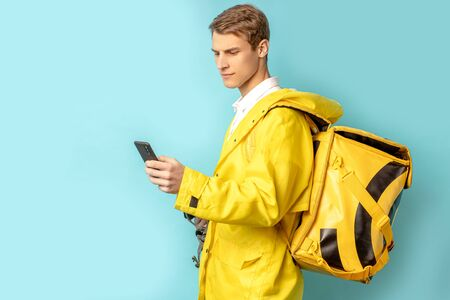attractive young caucasian guy 20-25 years old work as courier in delivery service, pleasant man in yelow uniform stand isolated over blue background Zdjęcie Seryjne