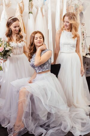 three young caucasian women with beautiful makeup and hair try on white wedding dresses together, dream to be bride, holding bouquet of flowers in hands and posing in salon among dresses Zdjęcie Seryjne