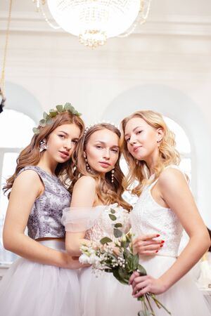 portrait of three beautiful brides or fiancee posing at camera together, wearing white wedding dresses, attractive romantic girls in wedding salon