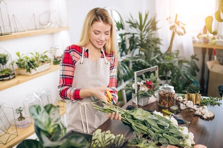 young caucasian florist at work, pretty young blond female making fashion modern bouquet of different flowers wearing red casual shirt
