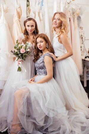 portrait of three attractive young ladies wearing fashionable airy dresses stand together in wedding salon, posing at camera. try on new dress by professional dress designer Zdjęcie Seryjne