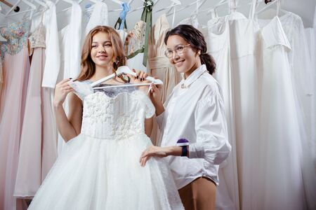 young good-looking caucasian bride going to buy wedding dress by designer in salon, try on it and look at mirror
