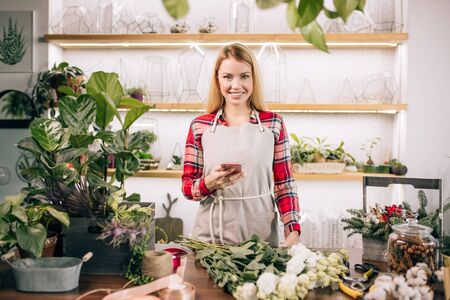 young attractive gardener at work, take care of green plants, enjoy working with flowers, isolated in room full of flowers and plants, botany concept