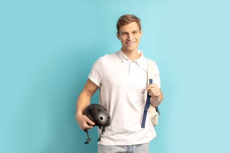 Portrait of positive young caucasian man wearing white t-shirt and holding motorcycle helmet for safety posing isolated over blue background. Motor sports, extreme lifestyle