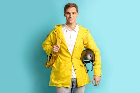 portrait of young caucasian man working in express delivery service, driving motorcycle, holding helmet and wearing yellow uniform isolated over blue background