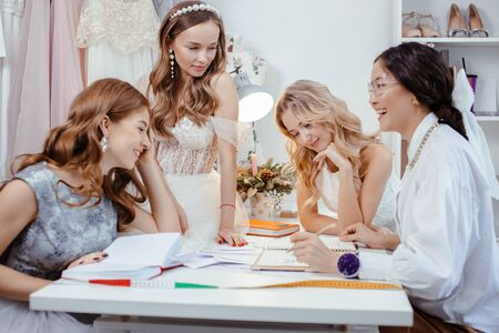 group caucasian models have conversation with designer and tailor of wedding dresses, have friendly conversation and consultation or advice: which style and type of dress is appropriate and for whom