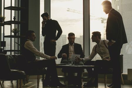 business coworking of young caucasian bearded men in office gathered to discuss business ideas, share experiences and opinions, successful cooperation of enthusiastic business people
