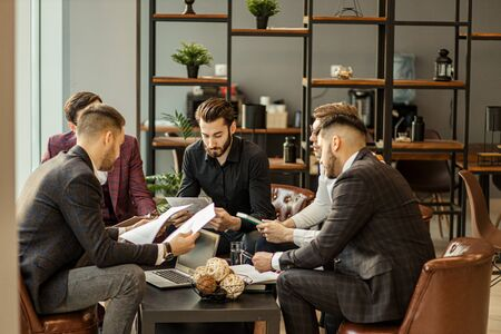 brainstorming time of business team consisted of young successful and confident guys in tuxedo, business crew coworking in modern office, creating and developing business projects
