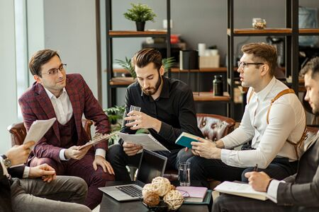 serious business people hold meeting in office for discussing and speaking about business projects, ideas and strategies for future. successful confident men in elegant suits indoors