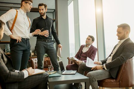 caucasian business people gathered in office for discussing business ideas and sharing experience, successful teamwork of leaders dressed in tuxedo