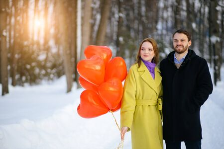 portrait of happy caucasian married couple celebrating anniversary outdoors. young man and woman in coats spend time at winter street, with red air balloons. love concept