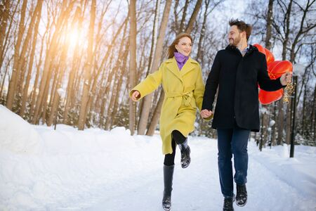 portrait of young happy caucasian couple in coats outdoors. beautiful emotional man and woman enjoy spending time together, walk and jump on street. relationships, love, emotions, people concept