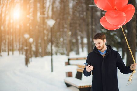 romantic guy with beard stand holding red air balloons, wait for his girlfriend on date,want to please. man look at screen of mobile phone, writing message. people, celebrating, romantic, love concept