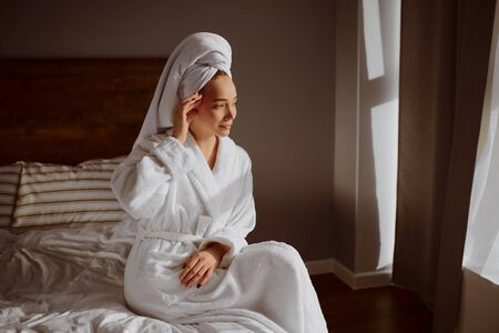 Beautiful young female spending morning time at home, sitting on bed, having sun shine on face, looking at window with positive feelings, dressed in bathrobe after shower 写真素材