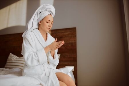 Charming young woman sitting on bed with depilatory sprigs in hands