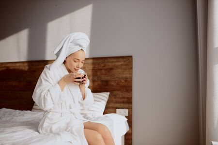 Pleasant tender girl in cozy bath clothes, enjoying loneliness at bedroom