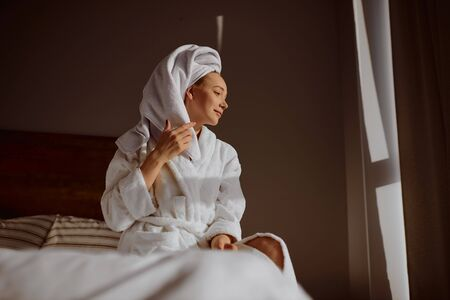 Portrait of young relaxed girl with white bath towel on head, resting in bedroom after shower, looking away at window, waiting for husband coming home, beauty and clean body concept