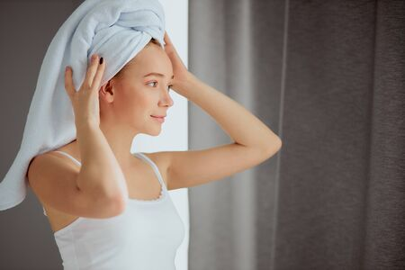 Pretty young woman wrapped head with bath towel, drying hair after shower, looking at window, waiting for friends, preparing for evening party, clean body treatment concept 写真素材