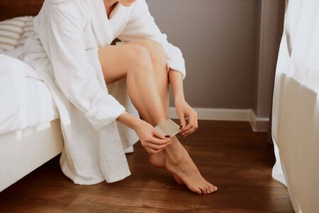 Young female sitting in bedroom with depilatory strip on leg 写真素材
