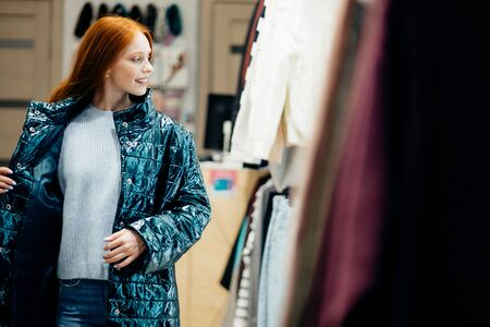 attractive caucasian woman try on coat and look at mirror in it, side view