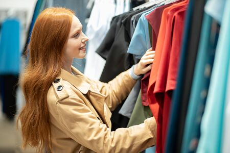 attractive woman with red hair happily looking for, searching beautiful clothes for herself, choosing best wear in shopping store 写真素材