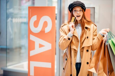 beautiful attractive female wearing coat, holding paper bags. happy joyful cheerful woman in clothes store , SALE background Reklamní fotografie