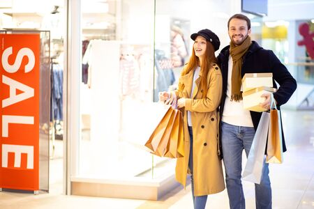 beautiful caucasian couple buy gifts, new clothes, bearded man hold gifts in hands, caucasian female with red hair holding paper bags