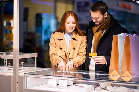 beautiful lovely cute couple in shopping mall together, decided to buy jewelry for woman, man holding discount card in hands going to buy ring