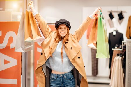 beautiful overjoyed woman with raised hands holding paper bags after successful shopping