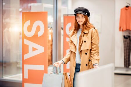 beautiful redhaired caucasian woman holding shopping paper bags, excited with shopping in store. SALE inscription in the background