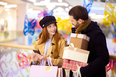 beautiful redhaired woman and bearded young man holding bags and gifts after shopping in mall. leisure time together